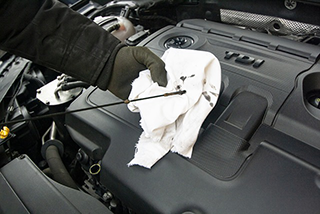 photo of mechanic cleaning oil with white towel from oil level indicator
