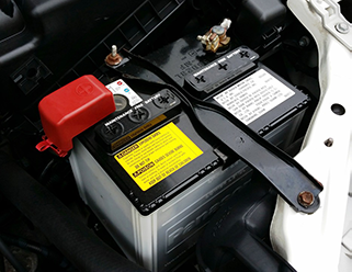 close up image of car battery inside of car engine bay